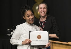 Student Kedine receives an award from the Communications Department.