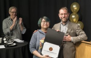 Student Jessica Cooper receives an award from the Communications Department.